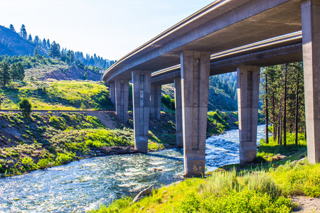 river banks: Large Highway Overpass Crossing River In Mountains