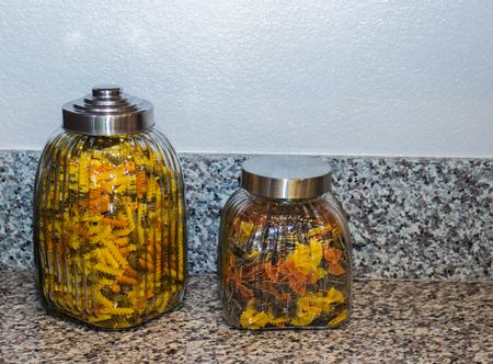 Two Pasta Jars On Granite Counter