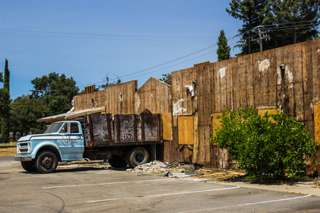 Truck Removing Debris From Boarded Up Building Stock Photo