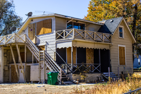 Abandoned Two Story Home With Boarded Up Windows & Doors