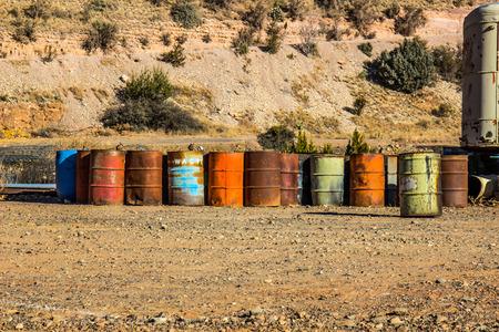 Row Of 50 Gallon Multi Colored Barrels In Salvage Yard