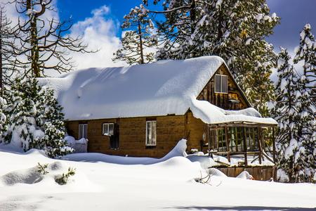 Toit couvert de neige sur la cabane en bois dans les montagnes Banque d'images - 99572395
