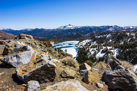 Boulders Overlooking Winter Lake With Snow Melting