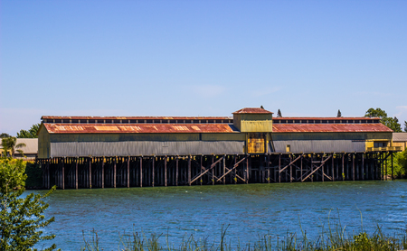 Long Rusty Tin Roof Building On Piers On Local Slough Stock Photo - 102241608