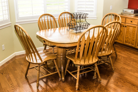 Wooden Table And High Back Chairs On Rich Hardwood Floor