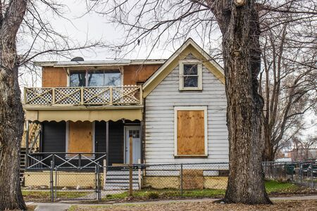 Abandoned Two Story Home With Boarded Up Windows