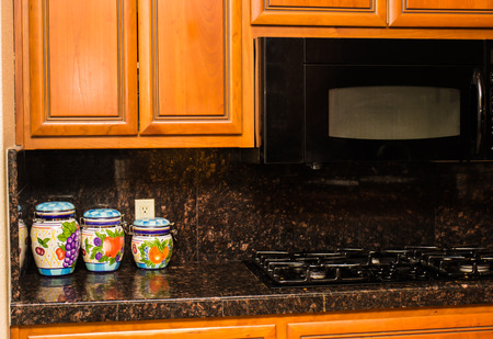 Three Ceramic Canisters On Granite Kitchen Counter