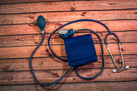 Blood Pressure Cuff & Stethoscope On Wood Table