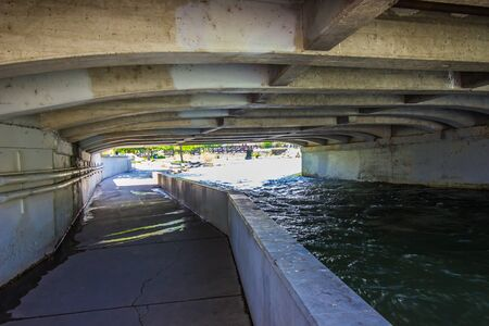Pathway Under Traffic Bridge Next To Rushing River