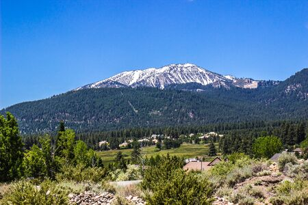 Snow Covered Mountain Overlooking Forest And Valley In High Desert