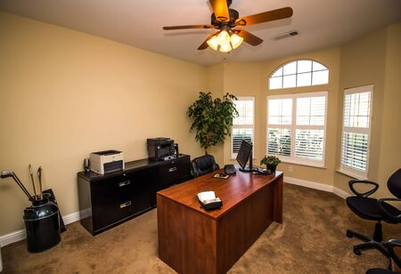 Office With Wooden Desk, Black File Cabinets & Office Equipment Stockfoto