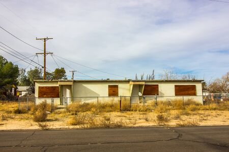 Run Down Duplex With Weeds And Boarded Up Windows