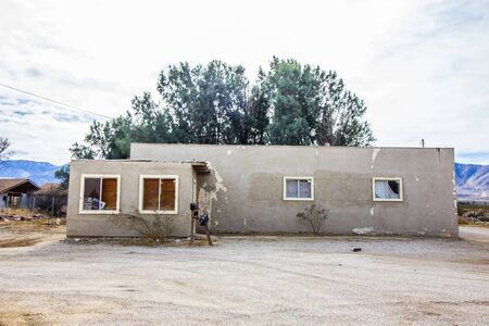 Abandoned Adobe Home With Peeling Paint & Boarded Up Windows Stock Photo
