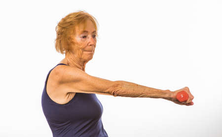 Senior Woman Concentrating On Lifting Two Pound Dumbbell In Front Of Her Body Standard-Bild
