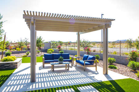Rear Yard Pergola Covering Two Couches With Blue Cushions & A Coffee Table