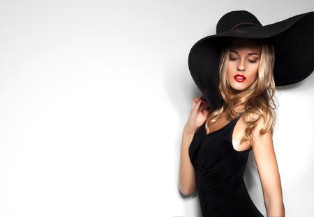 La alta manera tiró de mujer rubia con el pelo rizado en el sombrero negro y elegante vestido de noche elegante posando sobre fondo blanco estudio