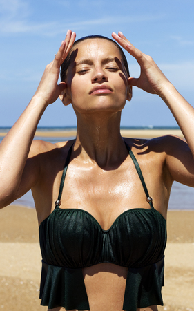 full lips: Sexy wet woman on beach. Beautiful gorgeous girl with full lips wearing green bikini poses going out from sea. Fashion look.