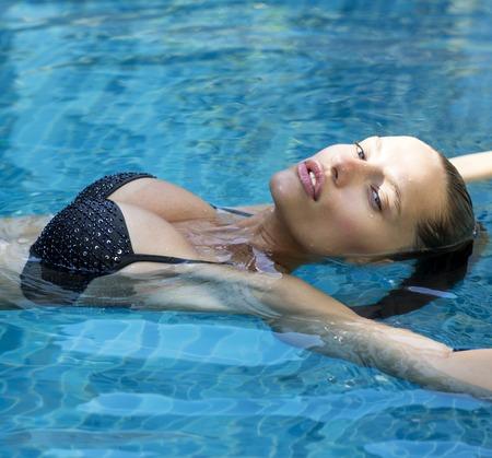 full lips: Beautiful fashion woman in pool. Sexy girl with full lips wearing stylish bikini poses at resort spa Stock Photo