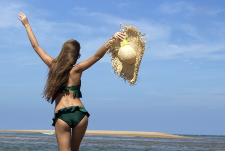 sunhat: Hot beautiful woman in sunhat, sunglasses and bikini standing with her arms raised up enjoying looking view of beach ocean on hot summer day. Vacation.Photo from Phuket island.