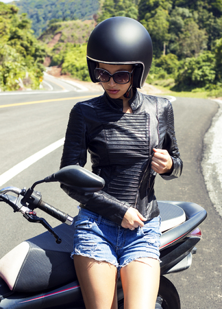pretty brunette woman: Beautiful woman in black helmet and leather jacket on scooter. Road of Phuket, Thailand