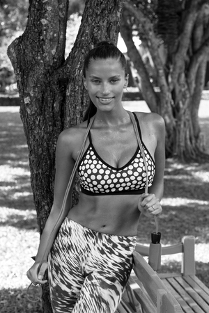 skipping rope: Sports woman in tropics with skipping rope wearing stylish sportswear after training. Phuket, Thailand Stock Photo