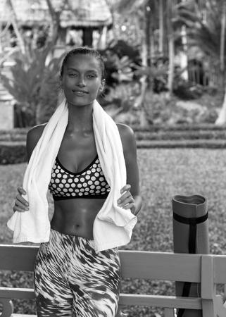 tropics: Sports woman in tropics with towel wearing stylish sportswear after training. Phuket, Thailand