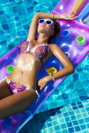 colorfully: Woman in sunglasses and bikini swimming on mattress in pool. Phuket, Thailand