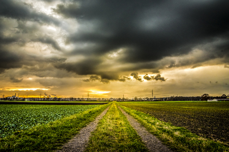 vanishing point: Old field path with houses extreme vanishing point perspective and dramatic sky. Stock Photo