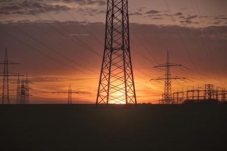 Sun sets over high-voltage line masts