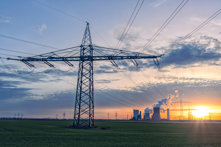 rwe: Sun sets over high-voltage line masts and power plant Stock Photo