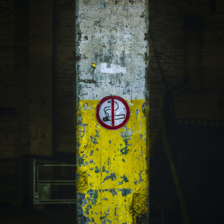 grey background texture: No smoking sign on old, damaged industrial building column painted in cigarette colors