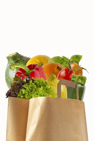 A paper bag filled with vegetables and fruits. Purchase of products.Isolated objects on white background. Stock Photo