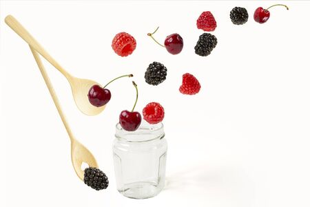 Assorted berries and wooden spoons with a jar of jam. isolated on white background.Cherries,blueberries,raspberries,mulberries and mint leaves in a chaotic free day the day . Summer harvest Reklamní fotografie