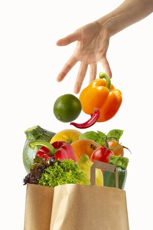 Female hand throwing vegetables in a paper bag with food.Isolated objects on white background.