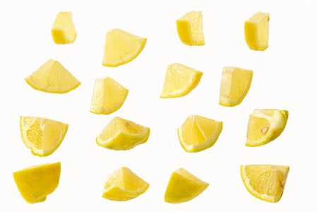 slices of sliced lemon isolated on a white background in a chaotic manner .