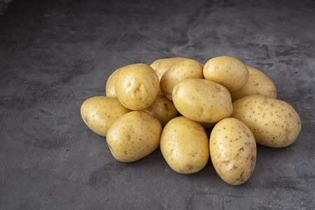 Young potatoes on a dark background.Crop. Harvest