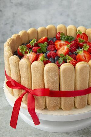 berry cake decorated with large strawberries,raspberries, blueberries on a light background. Festive pastries and sweet table. Summer berries and desserts. Preparation of confectionery.savoiardi biscu