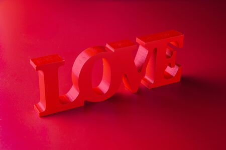 Background image on the theme of Love.Valentines day. Wooden word Love on red background.