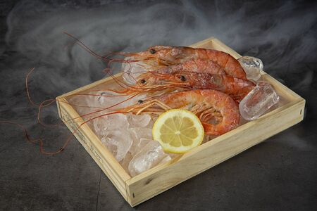 Red shrimp large on black background in wooden box . the view from the top. Marine food