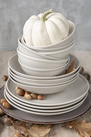 A stack of plates of different sizes on the table decorated with white pumpkin autumn leaves and nuts .