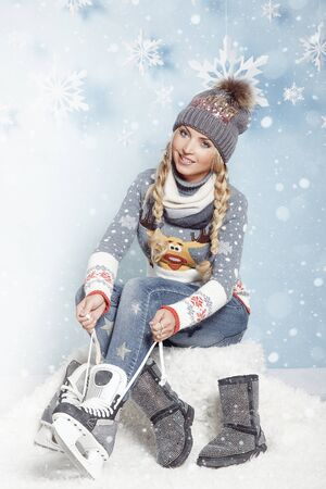 Blonde girl with long braids dressing skates, tightening laces. winter ice skating. Christmas holidays and entertainment.
