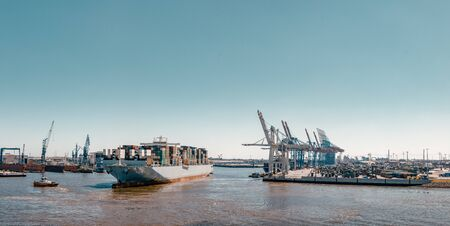 Container ship arrives at a terminal in the port of Hamburg 写真素材