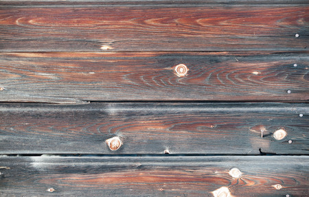 Knotholes and nails on a grungy wooden background