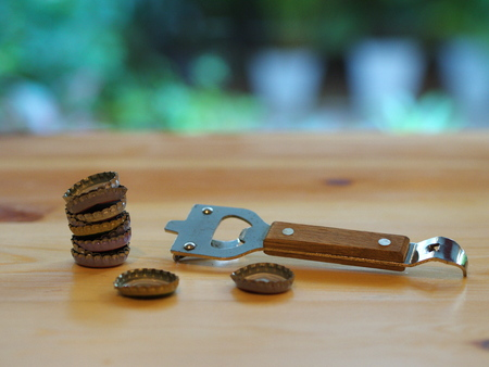 bottle opener: A Bottle Opener with a cap on a wooden table. Natural Light.