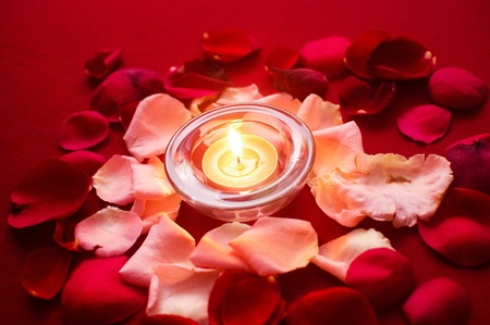 Burning candles surrounded with aromatic rose petals photo
