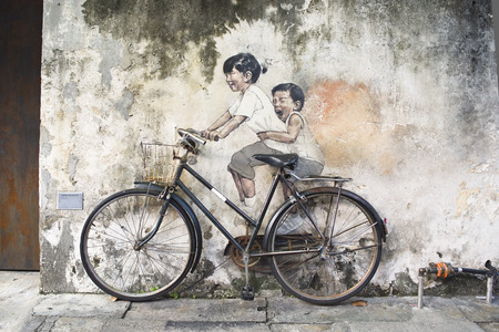 asian art: Little Children on a Bicycle or Sibling Cyclist Street Art Mural in Armenian Street, George Town, Penang by Lithuanian artist Ernest Zacharevic in George Town, Penang, Malaysia. Editorial