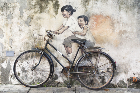 ernest: Little Children on a Bicycle or Sibling Cyclist Street Art Mural in Armenian Street, George Town, Penang by Lithuanian artist Ernest Zacharevic in George Town, Penang, Malaysia. Editorial