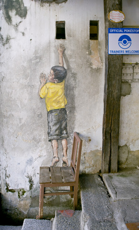 pinang: Street arts painting called reaching up or Boy on chair and can be found in canon street, George Town, Penang, Malaysia.