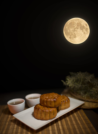 Chinese Mid Autumn Festival mooncake and tea on Wooden Bamboo Mat with Dark Background