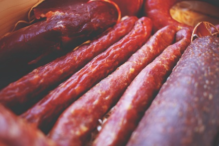 air dried salami: Assorted meat products including ham and sausages in a wooden box. Stock Photo
